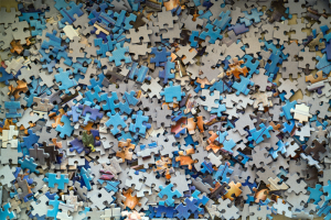 A jumble of jigsaw puzzle pieces. Managing technical debt can be like solving a puzzle.